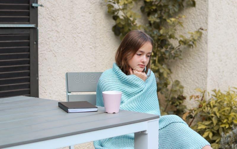 Fantasia pensativa bonita da moça envolvida na manta feita malha morna de turquesa que senta-se com o copo do chá e do livro fora imagens de stock royalty free