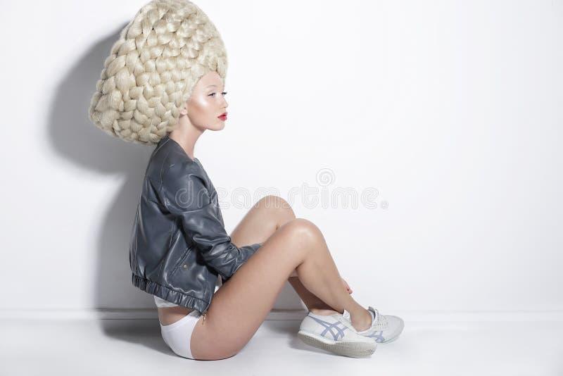 Fantasie u. Inspiration. Frau in der ungewöhnlichen Perücke mit dem falschen umsponnenen Haar stockbild