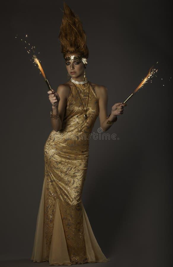 Fantasiebeeld van vlam-werpende vrouw in gouden kleermakerijen royalty-vrije stock fotografie