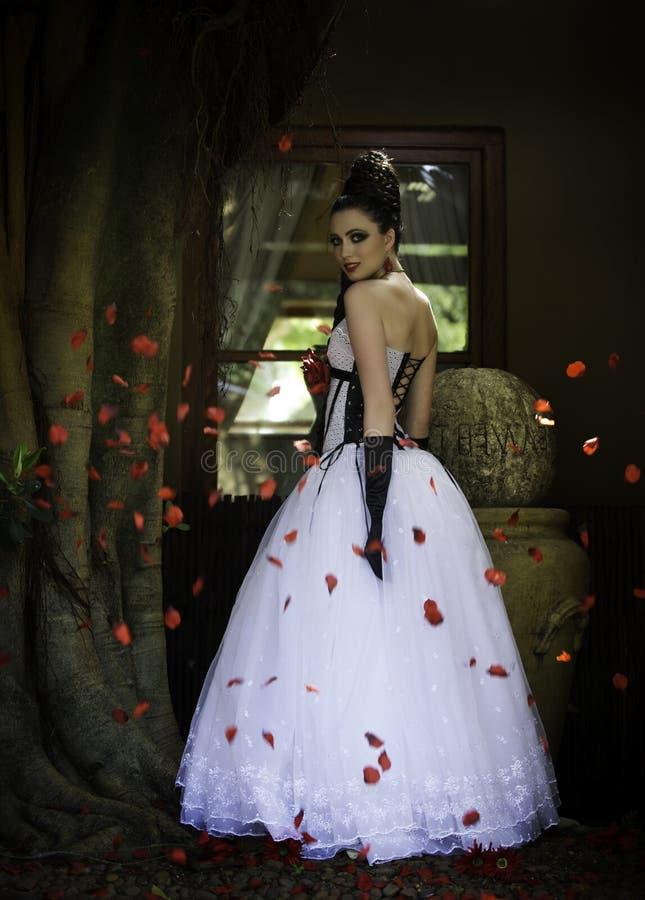 Fantasiebruid door rode roze bloemblaadjes wordt omringd dat stock foto's