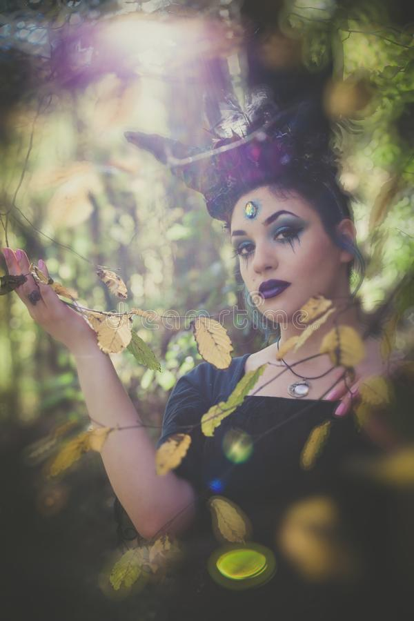 Fantasiefee mit Hörnern im Wald unter Bäumen und Niederlassungen lizenzfreie stockfotos