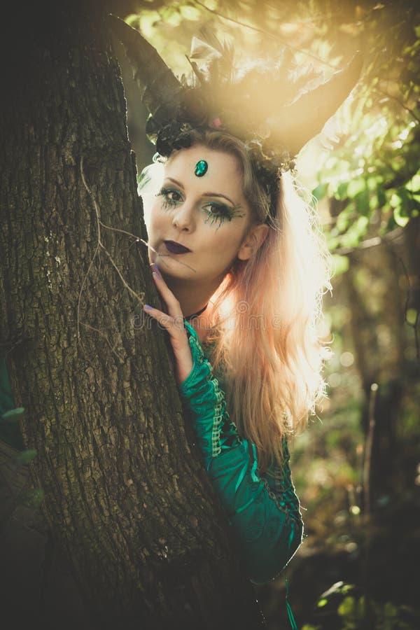 Fantasiefee mit Hörnern im Wald unter Bäumen und Niederlassungen stockbilder