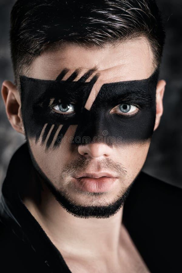 Fantasiekunstmake-up Mann mit Schwarzes gemalter Maske auf Gesicht Schließen Sie herauf Portrait Berufsmodemake-up lizenzfreie stockfotografie