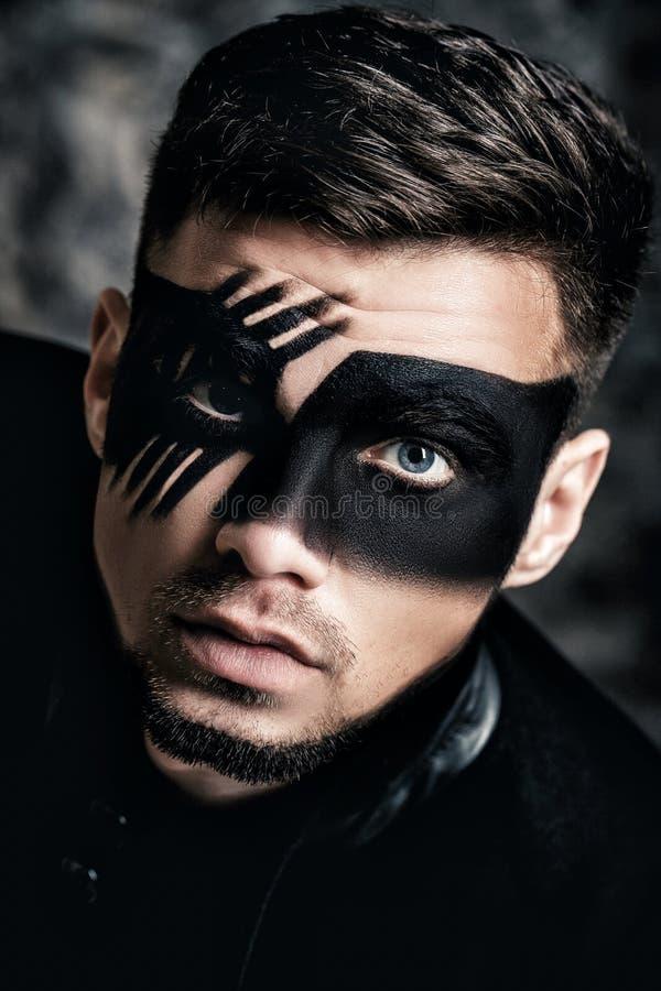 Fantasikonstmakeup Den unga mannen med svart målade maskeringen på framsidaslut upp ståenden Yrkesmässig modemakeup arkivfoton