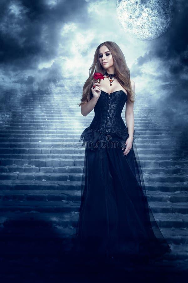 Fantasikvinna i svart klänning som luktar Rose Flower, mystikerflicka i lång Retro gotisk kappa royaltyfria foton