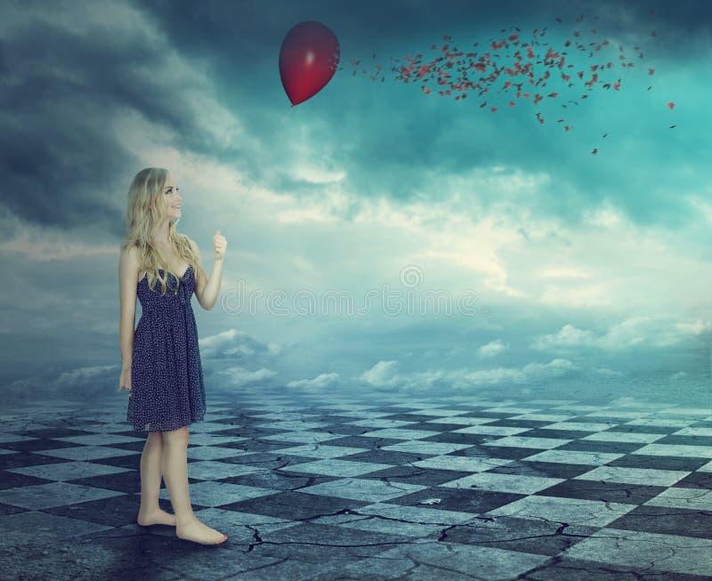 Fantasivärlden - ung kvinna som rymmer en röd ballong arkivbilder