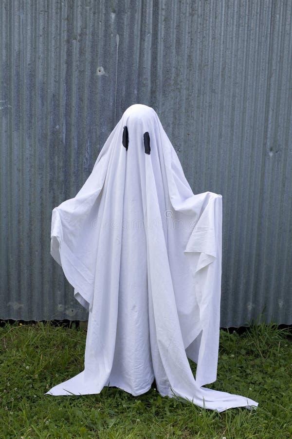 Fantasma branco na frente de uma porta da garagem imagens de stock royalty free