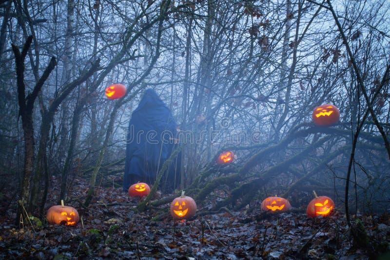 Fantasma con las calabazas de Halloween en bosque de la noche fotografía de archivo