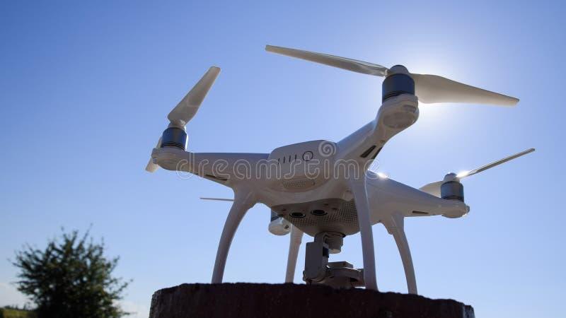 Fantasma 4 de Quadrocopter contra o céu azul no sol Luminoso Dron é um robô inovativo do voo imagem de stock
