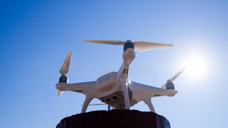 Fantasma 4 de Quadrocopter contra o céu azul no sol Luminoso Dron é um robô inovativo do voo imagens de stock