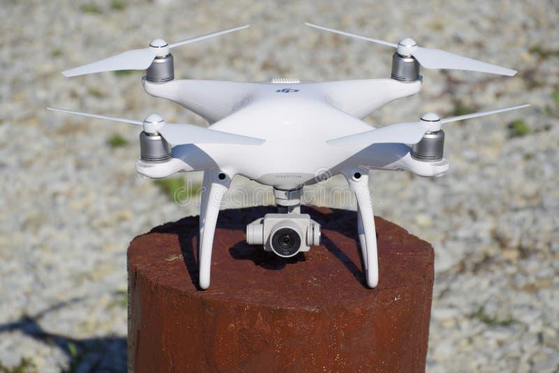 Fantasma 4 de Quadrocopter DJI em um cânhamo de madeira Preparando o zangão para o voo Dron é um robô inovativo do voo foto de stock royalty free