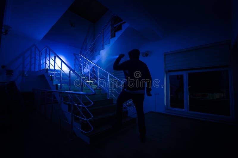 Fantasma en la casa encantada en las escaleras, silueta misteriosa del hombre del fantasma con la luz en las escaleras, escena de fotografía de archivo