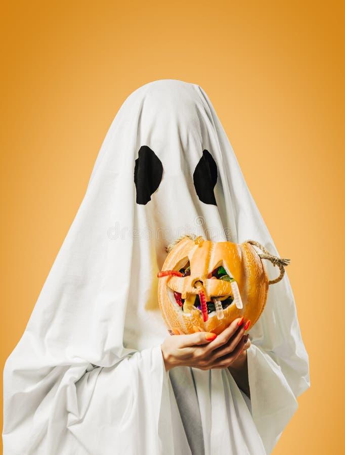Fantasma sostiene cesta de calabaza con caramelos en Halloween imagenes de archivo