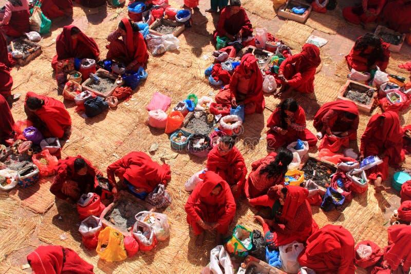 Fantaster som är klädda i röd saree, erbjuder böner på den Swasthani Matha templet royaltyfri bild
