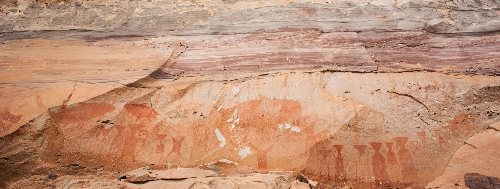 Fantastic ancient paintings on sandstone cliff, 3,000 year-old. Scene in paintings include giant Mekong catfish, elephants, stock image