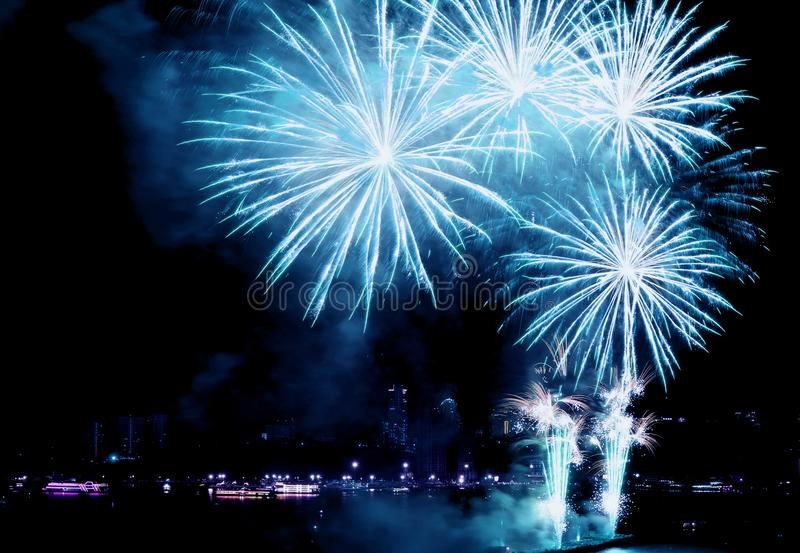Fantastic aqua blue color fireworks exploding in to the night sky over the bay stock photos