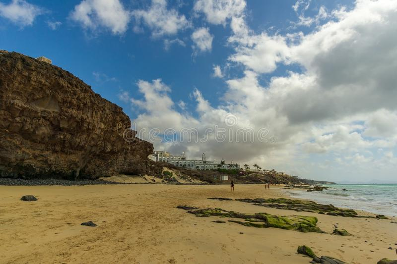 A fantastic beach with rocks and a big house. In the background stock photo