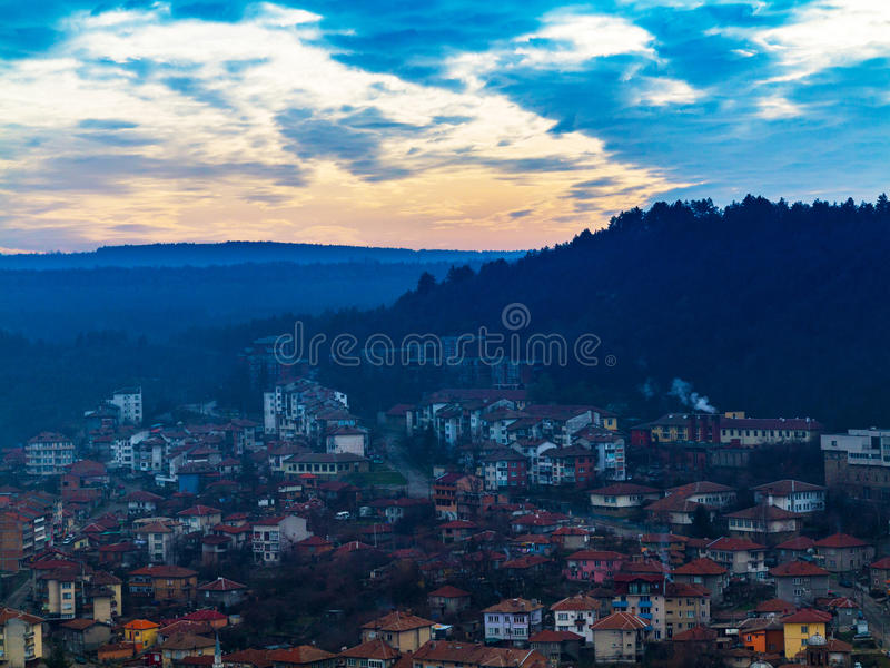 Fantastic beautiful cityscape at sunset with the horizon line di. Fantastic beautiful cityscape at dusk with the horizon line disappears in the fog. Image shows stock images
