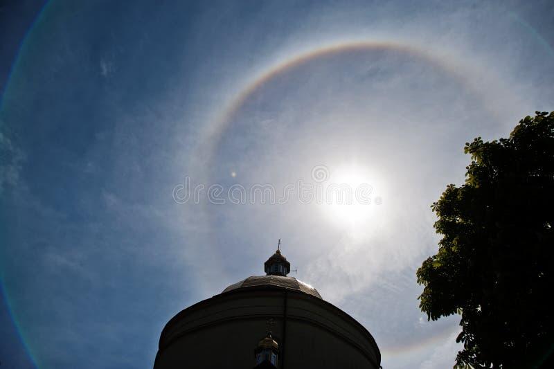 Fantastic beautiful sun halo phenomenon up the church, circular rainbow.  royalty free stock photography