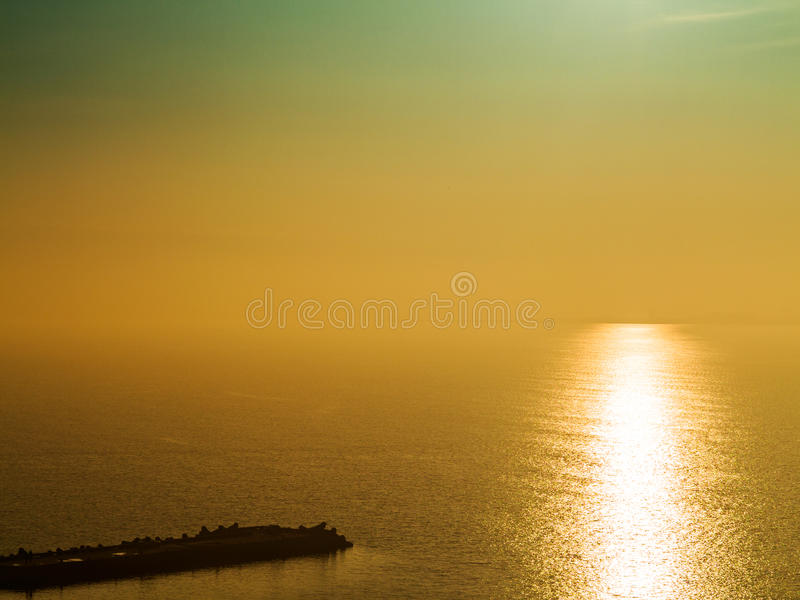 Fantastic beautiful sunset seascape with the horizon line disappears in the fog. Image shows a nice grain pattern at 100 percent stock image