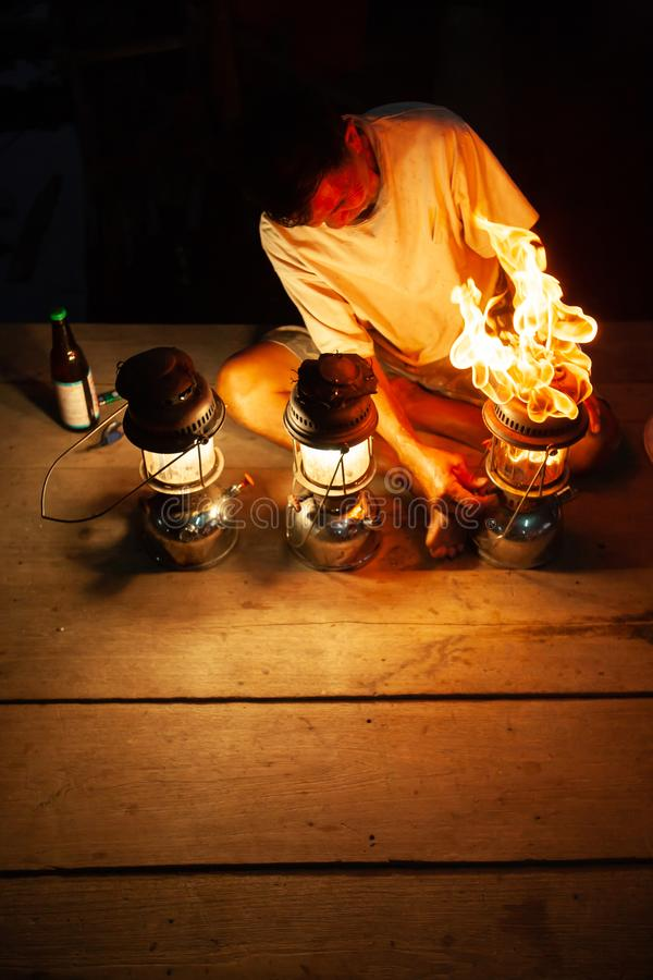 Fantastic fire flames, the old man with three vintage kerosene pressure lanterns on wooden at night, beautiful brightly burning royalty free stock photography
