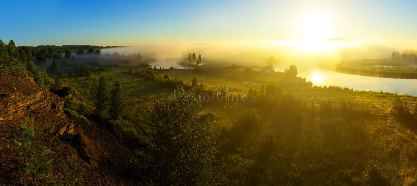Beautiful rural landscape in morning fog at sunrise. Temple on the river bank at sunrise, reflected in river stock images