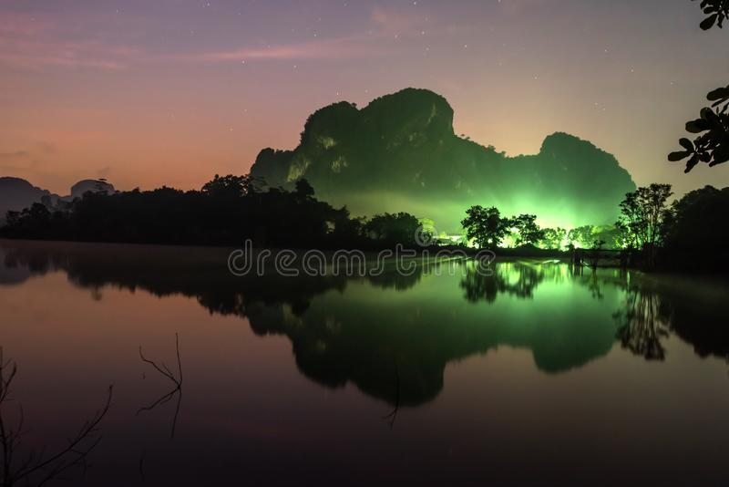 Fantastic landscape lake and mountains in the night with starry backgrounds. Lighting of village in front of the mountain. Sunrise stock images