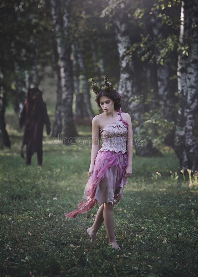 A fantastic love story. Girl Mystical fairy creature fawn in shabby clothes walking in the woods. Dark fantasy stock photos