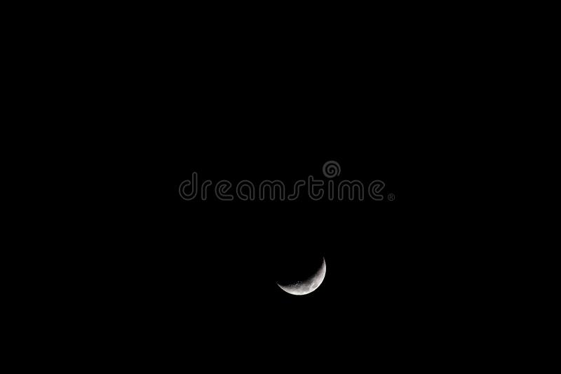 A fantastic moon, only a part of a moon`s face is illuminated. The other part remains in the darkness of the night royalty free stock photo