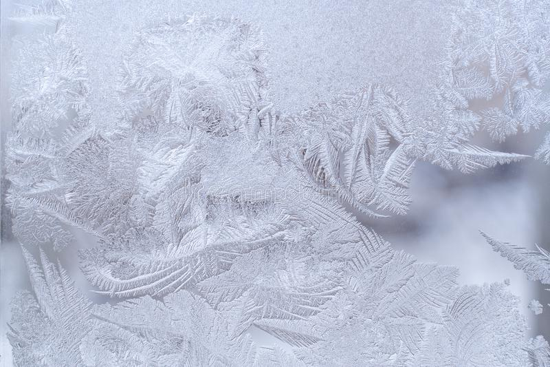 Fantastic ornate frosty pattern on winter window glass. royalty free stock photo