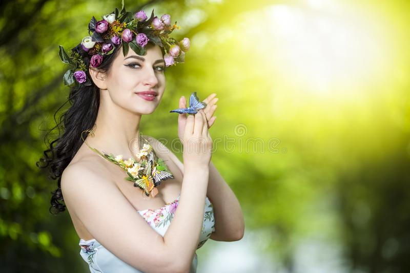 Fantastic Portrait of Sensual Brunette Female in White Dress Outdoors. Posing with Flowery Chaplet and Butterfly Against Sunlight. Horizontal image Orienation stock image