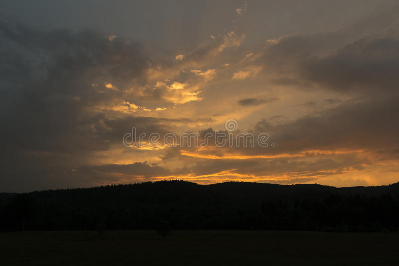Fantastic red sunset and dark ominous clouds stock photo