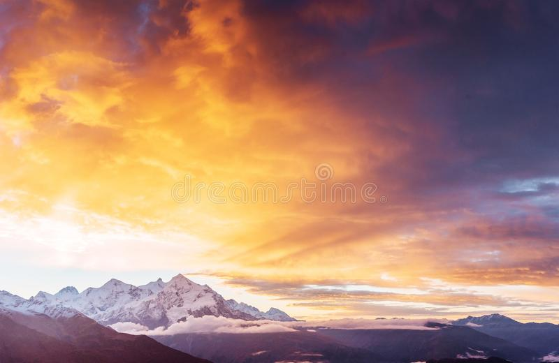 Fantastic snow-capped mountains in the beautiful cumulus clouds. Main Caucasian Ridge. Type Mount Ushba Meyer, Georgia.  royalty free stock image