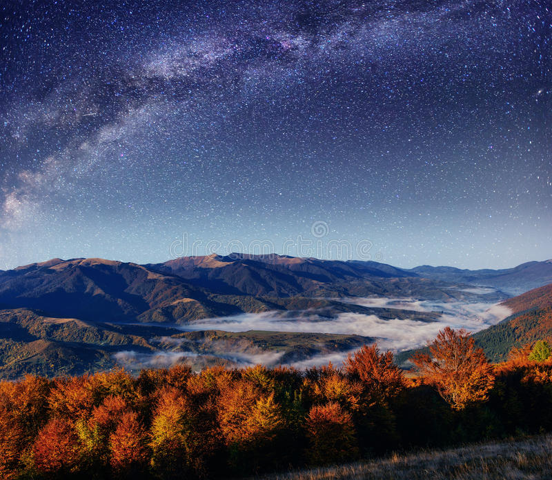 Fantastic starry sky and majestic mountains in the mist. Dramati stock photo