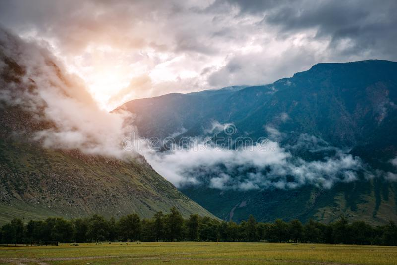 Fantastic sunrise with view into green valley and misty peaks. Colorful sunrise or sunset in the foggy summer mountains stock image