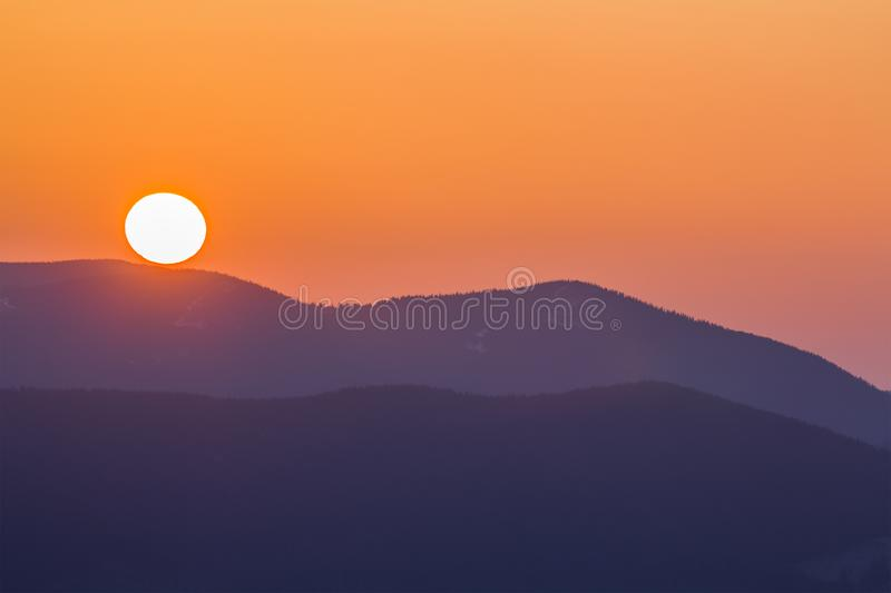Fantastic wide panorama view of big bright white sun in dramatic orange sky over dark purple mountain range at sunset or sunrise i royalty free stock photography