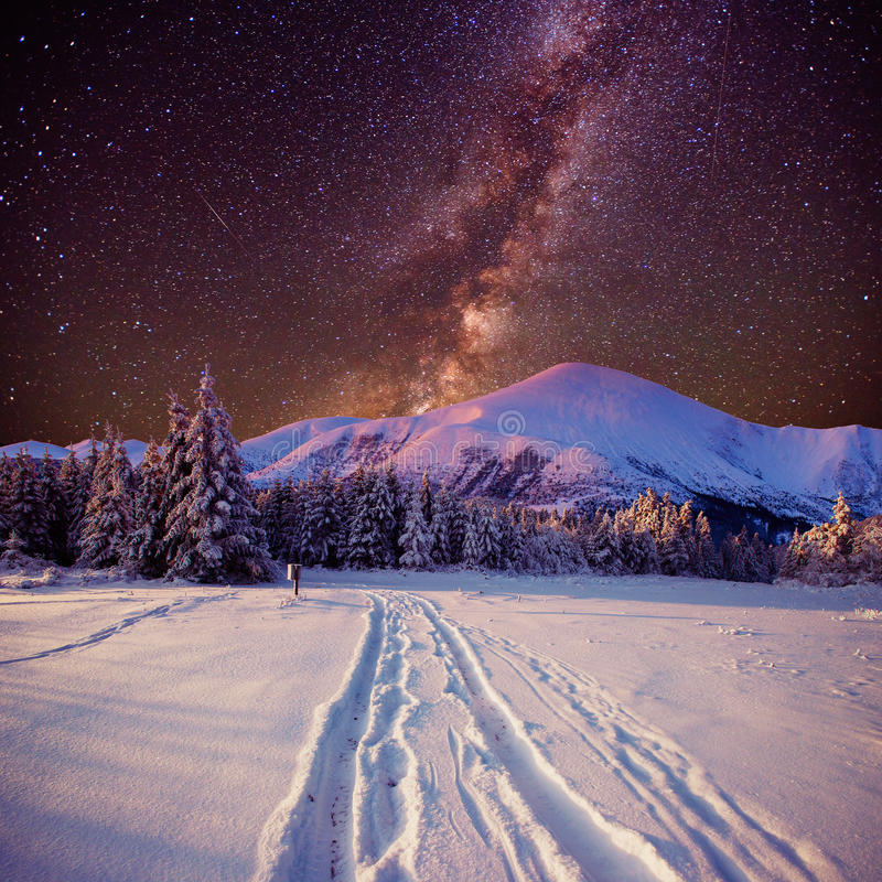 Fantastic winter meteor shower and the snow-capped mountains royalty free stock photos