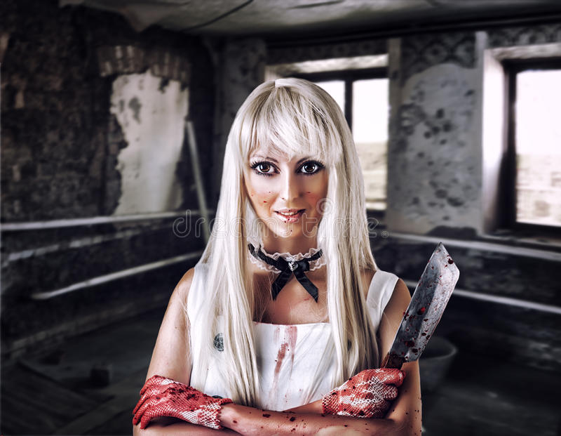 Fantastic woman in style of doll killer. Fantastic woman in the style of doll killer, zombie or a ghost with a bloody hatchet in hand royalty free stock photo