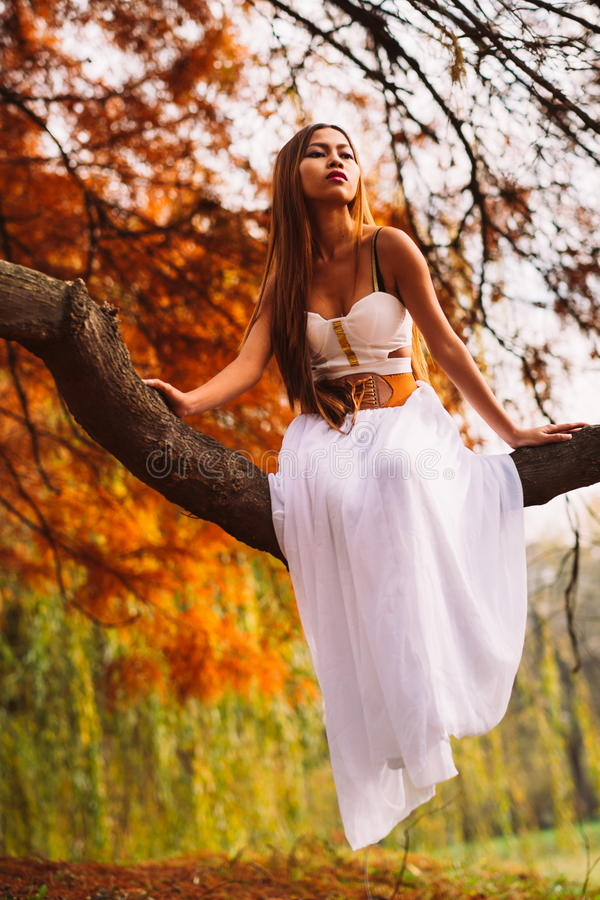 Fantastic young woman. beautiful fantasy girl fairy with white long dress in windy autumn park.  stock photos