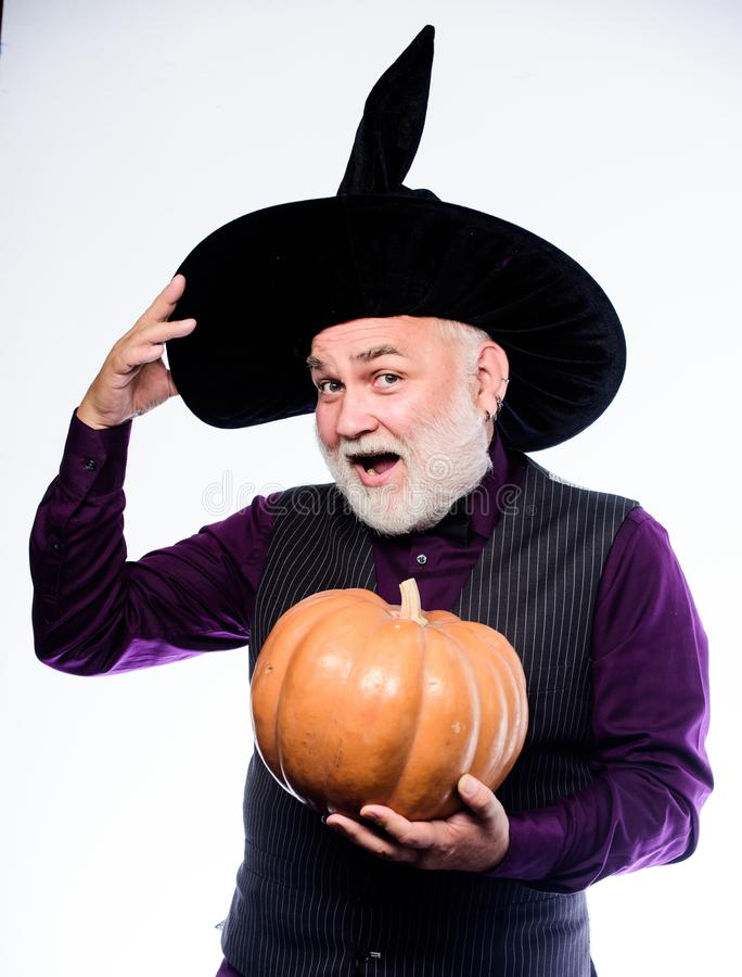 Fantastically good fun. Stargazer in holiday costume. Traditional food. bearded man ready for halloween party. evil. Wizard hold orange pumpkin. happy halloween stock images