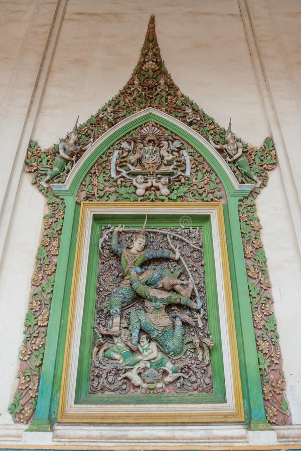 Fantastique sur le mur le filigrane de stuc de Narayana plie son arc sur le géant, un caractère de l'épopée de Ramayana Wat Damre image stock