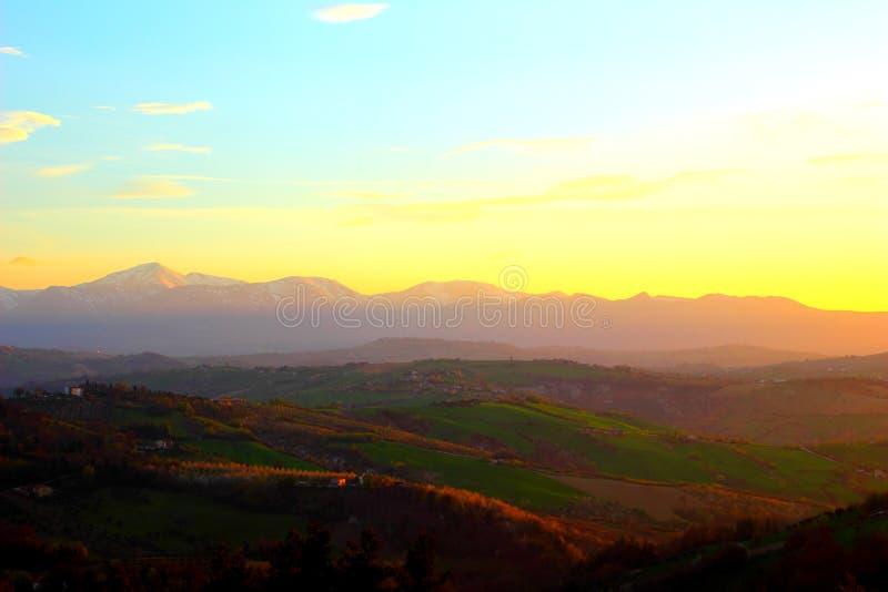 Fantastisch landschap met groene heuvels en Sibillini-bergen tijdens zonsondergang royalty-vrije stock afbeeldingen