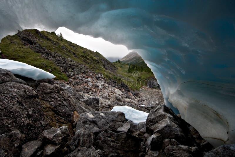 Fantastische blauwe ijsvorm tegen bergvallei stock foto's