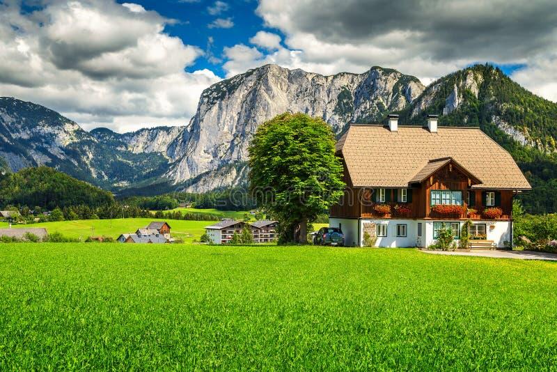 Fantastische Grünfelder mit alpinen Häusern und Bergen, Altaussee, Österreich stockfotos