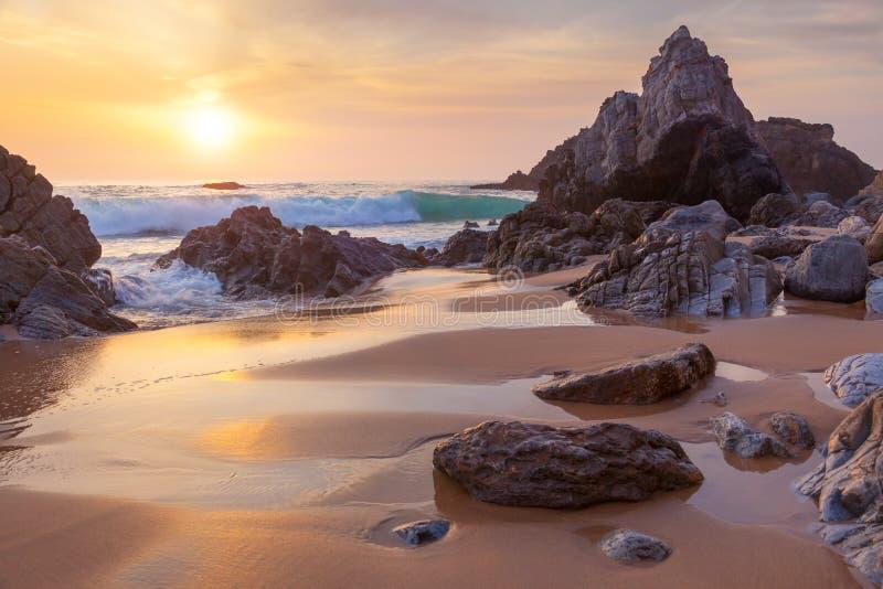 Fantastische grote rotsen en oceaangolven bij gouden zonsondergang royalty-vrije stock foto's