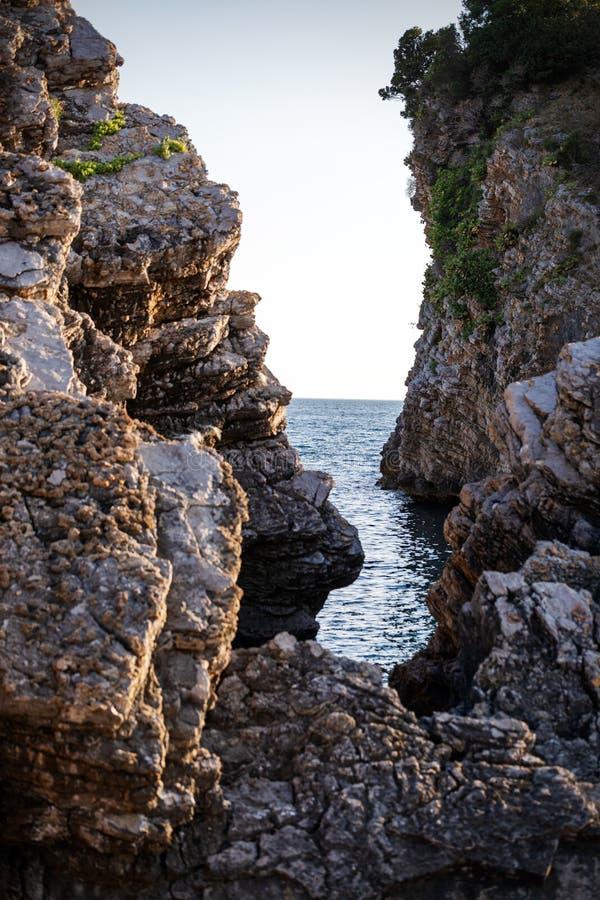 Fantastische grote rotsen en oceaangolven in zonsondergangtijd royalty-vrije stock foto