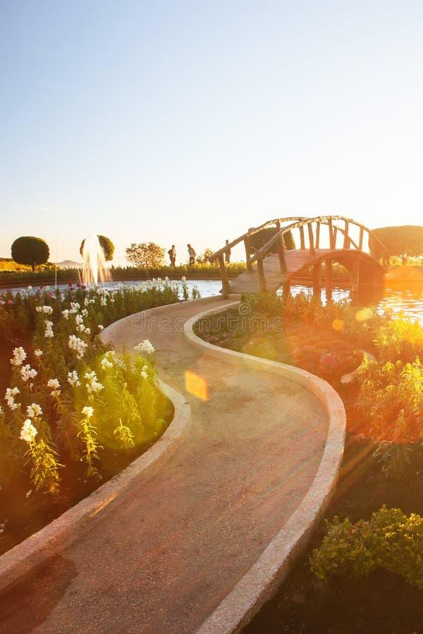 Fantastische Landschaft des tropischen Gartens mit Brunnen bei Sonnenuntergang, Einstellung des hellen Sonnenscheins mit schönem  stockfoto