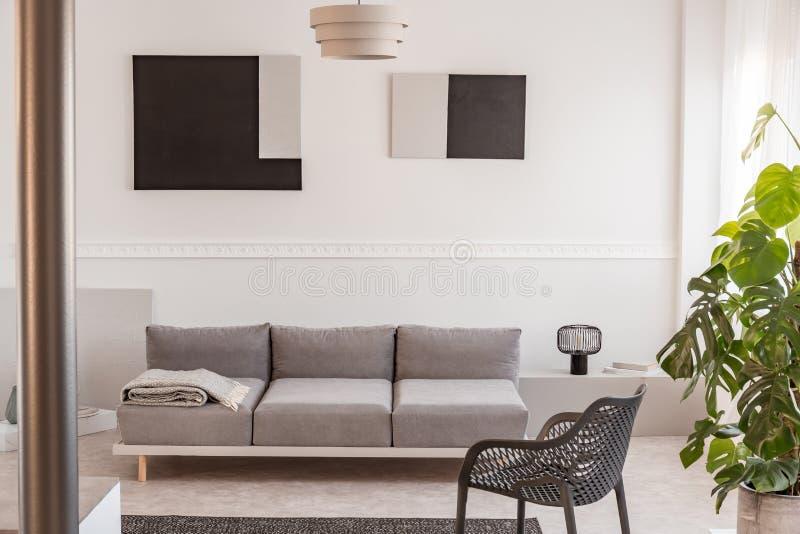 Fantastischer grauer Metallstuhl nahe bei bequemer Couch im hellen Wohnzimmer lizenzfreies stockbild