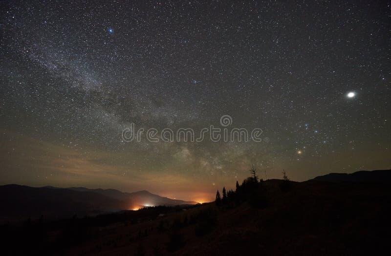Fantastischer Mountain View nachts Tannenbaumschattenbilder gegen dunkelblauen Himmel mit dem Funkeln spielt die Hauptrolle stockfotografie