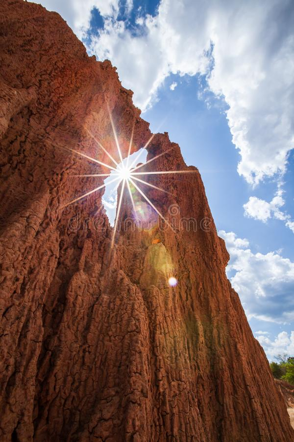 Fantastischer steil sediment?rer roter Sand in einer W?ste, sonniger Sternstrahl, Wolken mit leicht- Blau - Himmelhintergrund Abs stockfotos